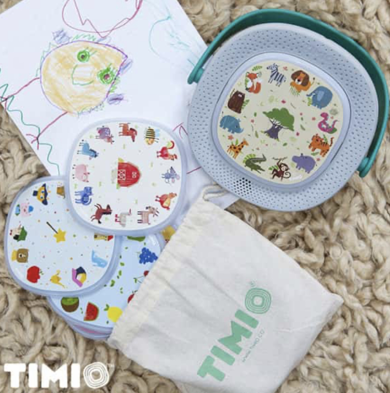 Timio toy and discs laied on carpet next to a child's drawing